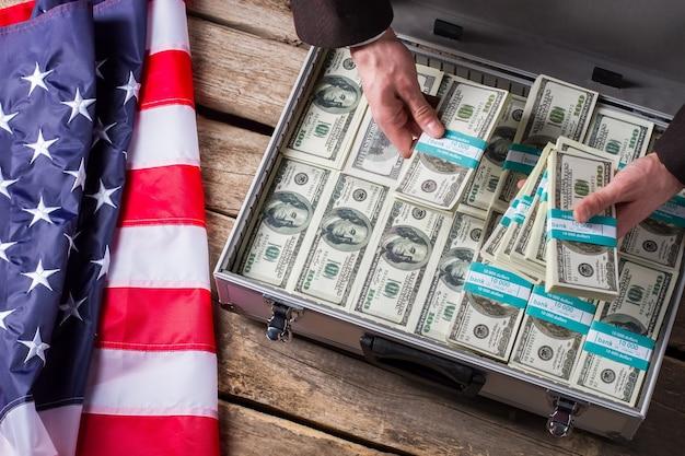 Руки держат пачки долларов. наличные деньги, руки и американский флаг. пора делать притон. большой доход может нести опасность.