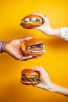 노란색 배경에 햄버거를 들고 손입니다. 패스트 푸드, 정크 푸드 개념입니다.