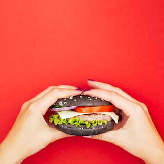 Hands holding a burger with lettuce