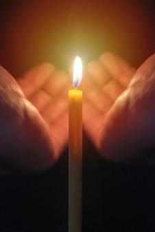 Руки с горящей свечой от ветра