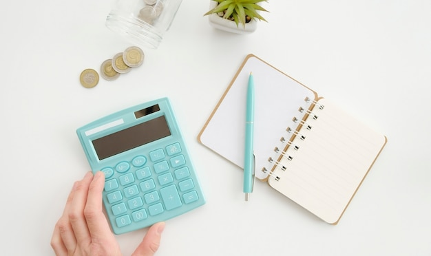 白いテーブルに電卓、コイン、ペンを持っている手。上面図