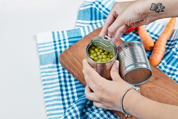 Hands holding a can of boiled green peas on a white table with vegetables and tablecloth.
