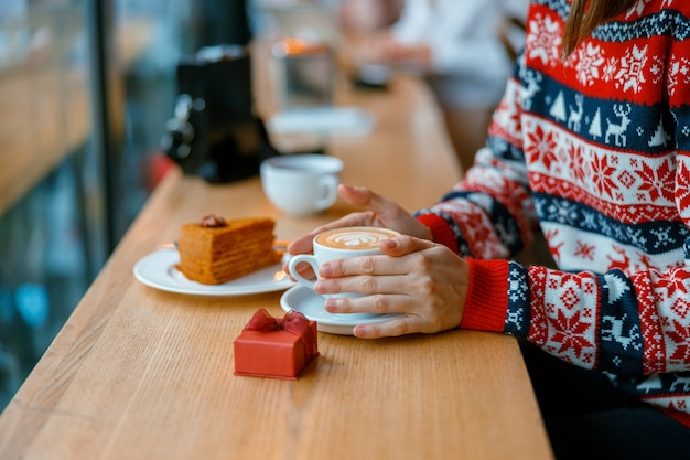 Hands holding a capuchino cup with gift box and cake on a cozy cafe terace