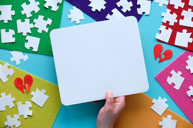 Руки держат картонную страницу с пространством для текста. плоская планировка, вид сверху на творческую аранжировку.