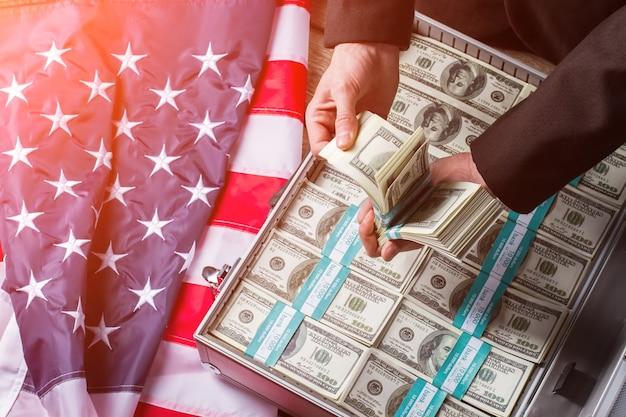 Руки держат наличные возле чемодана. флаг сша, руки и деньги. каждое решение приносит результат. меньше слов - больше дела.