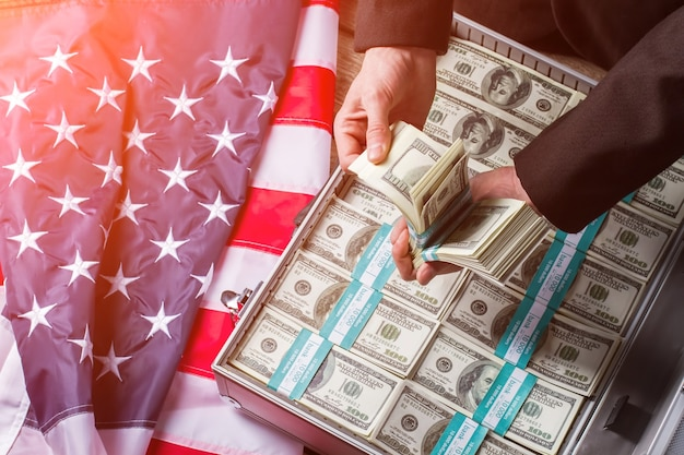 Hands holding cash near suitcase. usa flag, hands and money. every decision brings results. less words more deeds.
