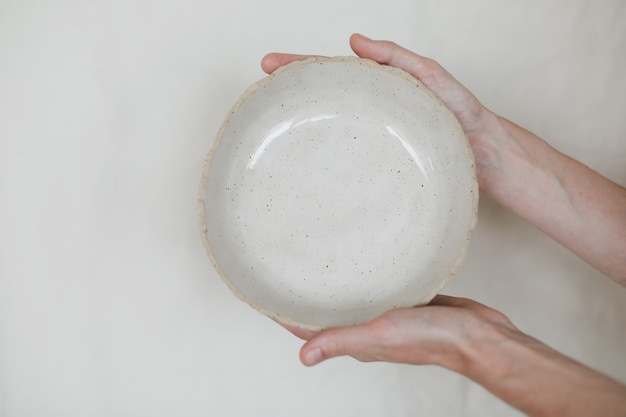 Руки держат керамическую чашу на белом фоне керамической посуды ручной работы и керамики
