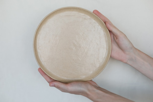 Руки держат керамические тарелки на белом фоне минималистский набор керамических столешниц ручной работы ...