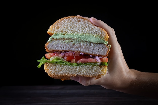 Hands holding a chicken burger with lettuce, tomato, purpple onion and handmade mayo on black backgorund. delicious.