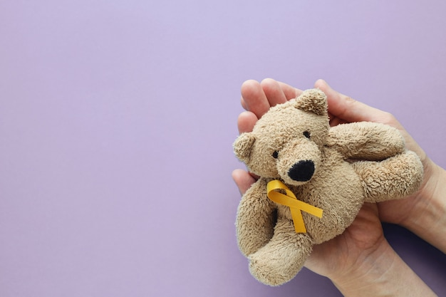 Hands holding children soft toy brown bear with yellow gold ribbon on purple background
