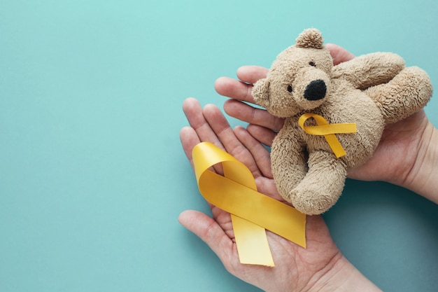 Hands holding children soft toy brown bear with yellow gold ribbon