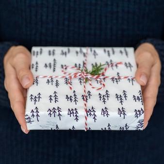 Mani che tengono il regalo di natale con lo spago e la foglia della caramella