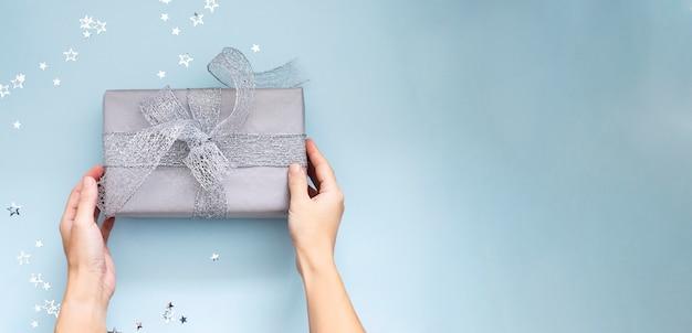 Руки держат рождественский подарок, обернутый серебряной лентой на голубом