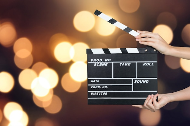 Hands holding clapper board on blurred background