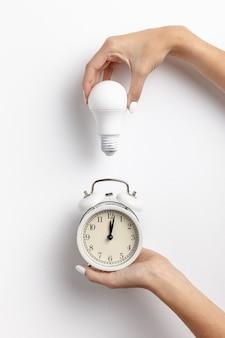 Руки держат часы и лампочку