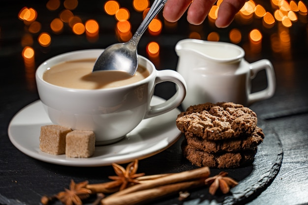 Hands holding coffee cookies and spices on blurred lights. stylish winter flat lay.