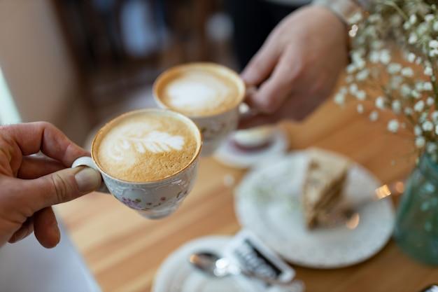 Руки держат кофейные чашки