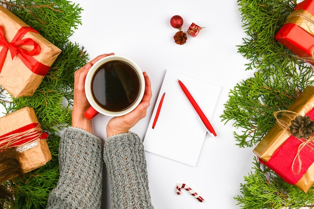 Hands holding a coffee mug on a christmas space. view from above. female hands holding coffee cup. christmas gift boxes and snow fir tree above wooden table. top view with copy space.