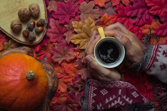 Hands holding coffee on autumn leaf composition