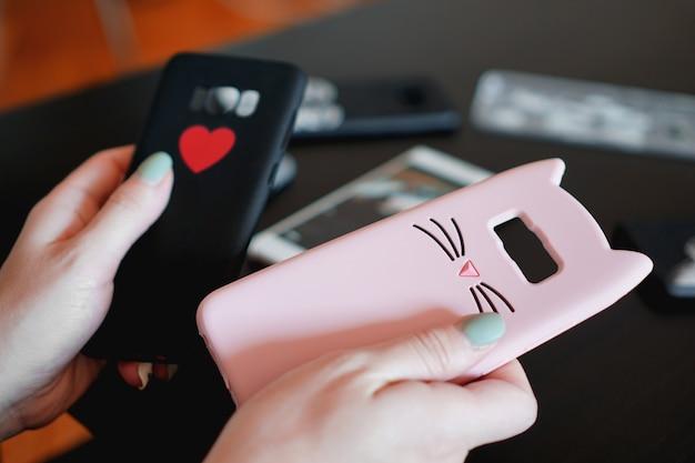カラフルなスマートフォンケースを持っている手。黒とピンクのスマートフォンケースからお選びください