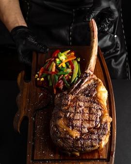 Hands holding cooked tomahawk (long bone ribeye) steak on a serving board. low key image, vertical orientation