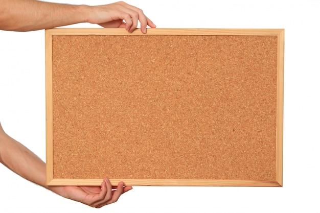 Hands holding cork board