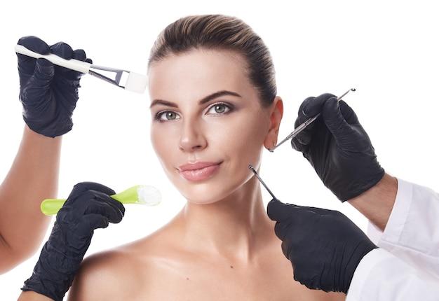 美しい白人女性の顔の周りに化粧ヘラ、ブラシ、美容ツールを保持している手