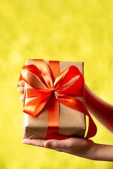 Руки держа подарочную коробку корабля с красной лентой на абстрактной предпосылке bokeh. вертикальный снимок. Premium Фотографии