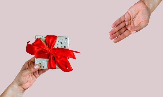 파란색 배경에 크리스마스, 새해, 발렌타인 데이 또는 기념일을 위한 선물로 공예 종이 선물 상자를 들고 있는 손