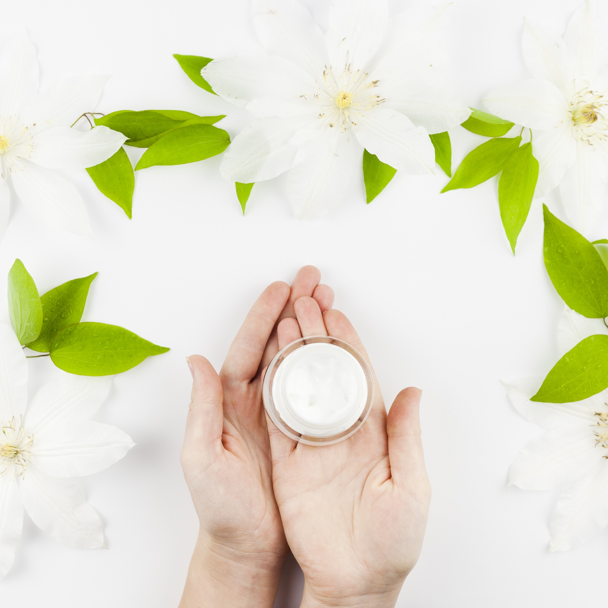 Hands holding cream with flowers around