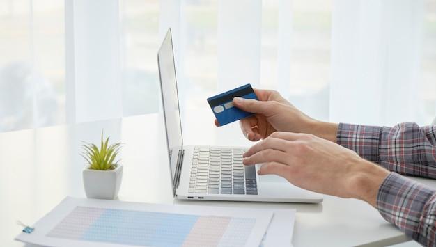 Руки держат кредитную карту и используют ноутбук. онлайн покупки