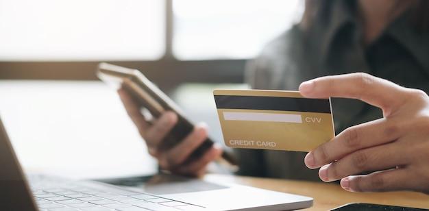 Руки держат кредитную карту и используют ноутбук. покупки в интернет магазине