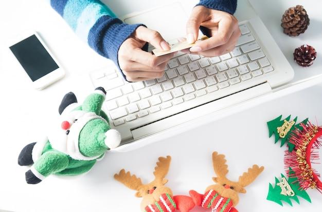 Руки, держащие кредитную карту и использующие ноутбук, смартфон с рождественским украшением, покупки онлайн