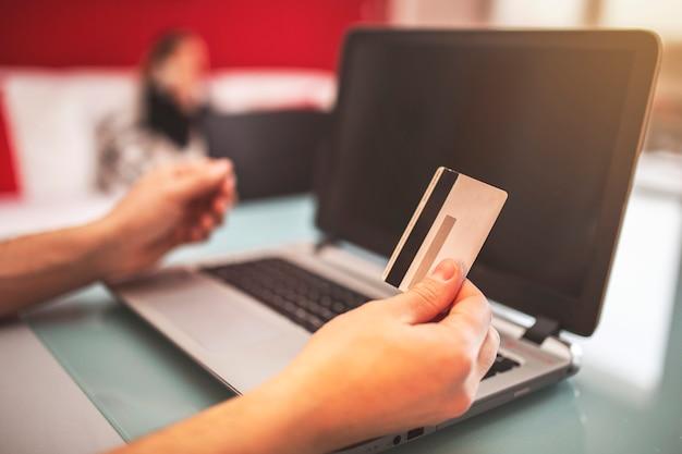 Руки держат кредитную карту и используя ноутбук.