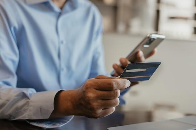 Руки держат кредитную карту и используют смартфон и ноутбук. онлайн покупки.