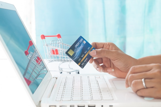 Hands holding credit card and using laptop computer with shopping cart background.