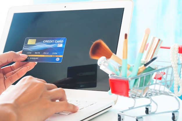 Hands holding credit card and using laptop computer.