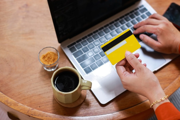Hands holding credit card and using laptop for online shopping payment