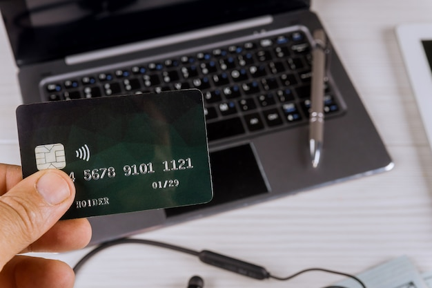 Hands holding credit card using laptop with online shopping