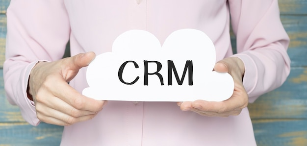 Hands holding crm text on a white cloud close up