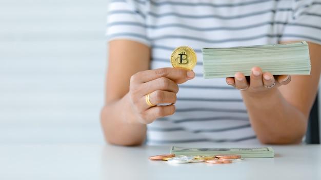 암호 화폐와 지폐 더미를 들고 있는 손과 비교 제스처. 디지털 자산과 구식 보물에 대한 투자의 개념.