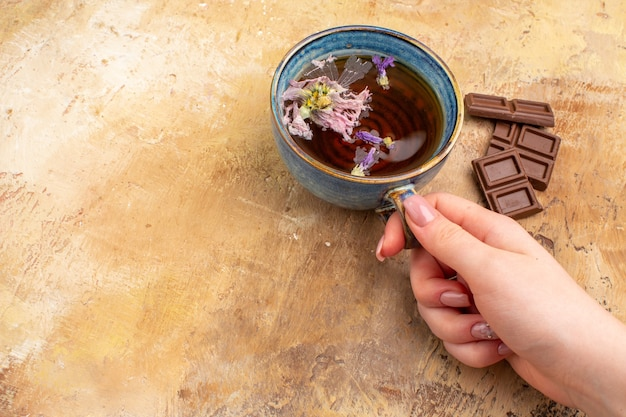 Hands holding a cup of hot herbal tea and chocolate bars on mixed color table