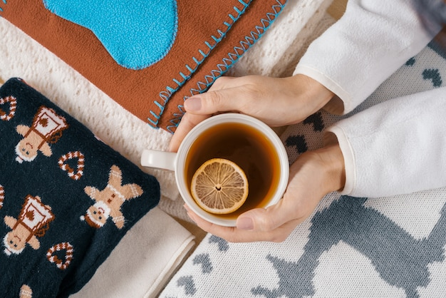 Hands holding cup of hot tea, background warm clothes