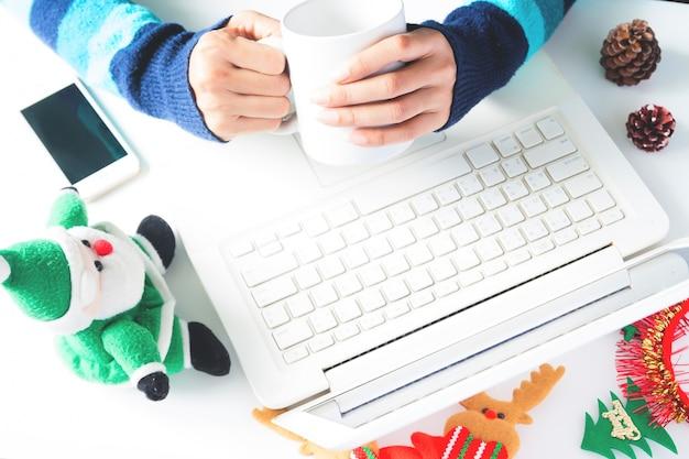 Руки, держащая чашку кофе и используя ноутбук, смартфон с рождественским украшением, покупки онлайн