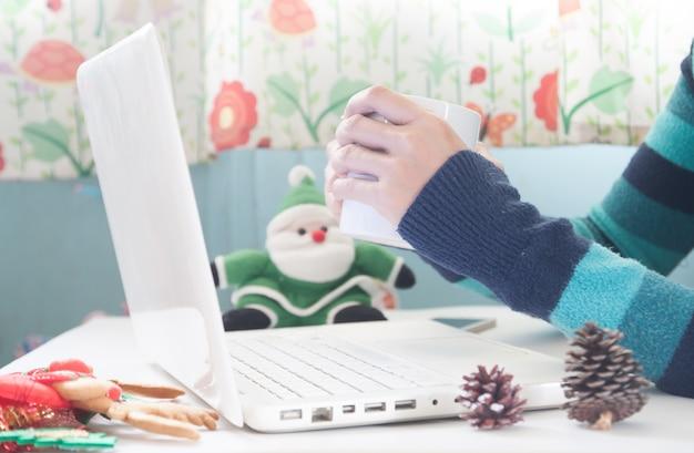 Руки, держащая чашку кофе и используя ноутбук с рождественским украшением, покупки онлайн