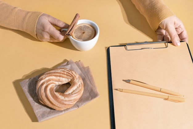 Hands holding cup of tea or mulled wine near resume sheet and cake on the set sail champagne colour background, top view.
