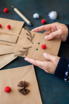 Hands holding cute reindeer decorated christmas present bag
