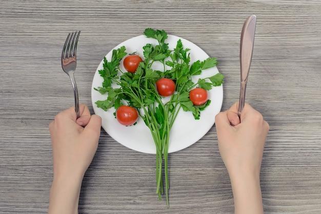 皿にカトラリーパセリとチェリートマトを持っている手