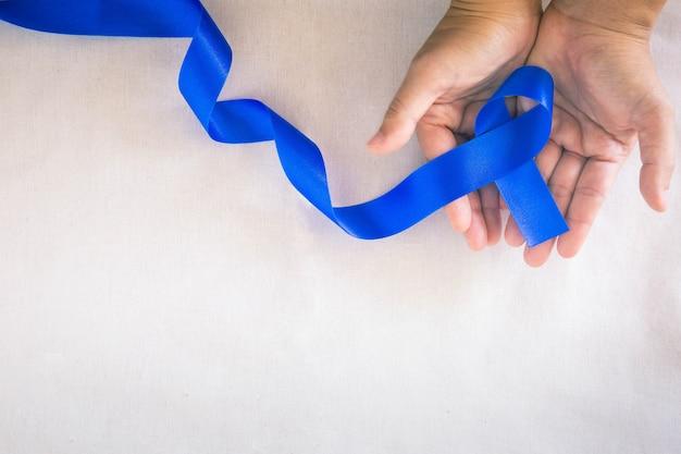 コピースペースのある白い布に深い青色のリボンを持っている手結腸直腸癌の認識高齢者の結腸癌と世界糖尿病デー児童虐待防止医療保険の概念