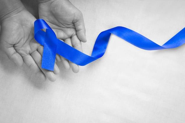 Руки держат темно-синюю ленту на белой ткани с копией пространства